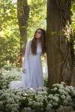 Mujer hermosa que lleva un vestido blanco largo que se inclina en un árbol Imagen de archivo libre de regalías