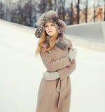 Mujer hermosa que lleva una chaqueta del sombrero y de la capa sobre nieve en invierno Fotografía de archivo libre de regalías