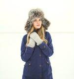 Mujer hermosa que lleva una chaqueta y un sombrero de la capa sobre nieve en invierno Imagen de archivo libre de regalías