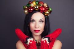 Mujer hermosa que lleva una guirnalda hecha de decoraciones de la Navidad Fotos de archivo libres de regalías