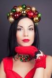 Mujer hermosa que lleva una guirnalda hecha de decoraciones de la Navidad Imagenes de archivo