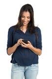 Mujer hermosa que manda un SMS con el teléfono Imagen de archivo