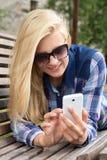 Mujer hermosa que manda un SMS con su teléfono en banco en parque Foto de archivo