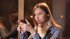 Mujer hermosa que manda un SMS en smartphone en café 4K almacen de metraje de vídeo