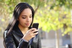 Mujer hermosa que manda un SMS en un teléfono elegante en un parque Fotografía de archivo