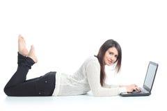 Mujer hermosa que miente con una computadora portátil Fotos de archivo libres de regalías