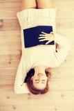 Mujer hermosa que miente en el piso con el libro Foto de archivo libre de regalías