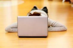 Mujer hermosa que miente en el piso con el ordenador portátil Foto de archivo libre de regalías