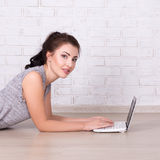 Mujer hermosa que miente en el piso y que usa el ordenador portátil en casa Foto de archivo libre de regalías
