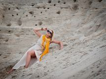 Mujer hermosa que miente en la arena fotografía de archivo