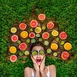 Mujer hermosa que miente en la hierba con las frutas alrededor de su pelo  Fotos de archivo libres de regalías