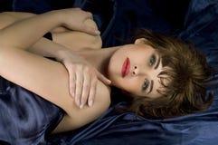 Mujer hermosa que miente en la seda azul marino Imagenes de archivo