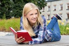 Mujer hermosa que miente en parque con el libro Foto de archivo libre de regalías