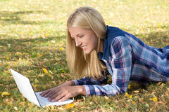 Mujer hermosa que miente en parque del otoño y que usa el ordenador portátil Imagen de archivo libre de regalías