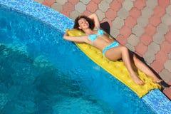 Mujer hermosa que miente en un colchón cerca de piscina Fotografía de archivo