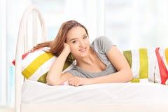Mujer hermosa que miente en una cama y que se relaja foto de archivo