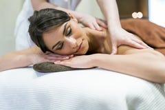 Mujer hermosa que miente en una tabla del masaje y que se relaja foto de archivo