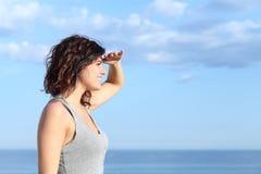 Mujer hermosa que mira adelante con la mano en frente Imagen de archivo libre de regalías