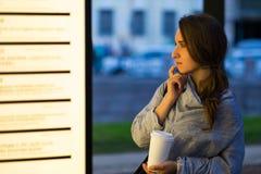 Mujer hermosa que mira con interés en la cartelera en blanco que decide adonde ir Imagenes de archivo