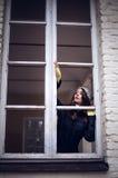 Mujer hermosa que mira con la ventana y el temor algo Foto de archivo libre de regalías
