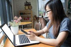 Mujer hermosa que mira en el ordenador portátil Imagen de archivo libre de regalías