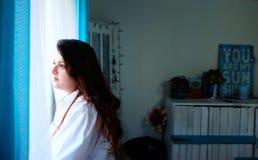 Mujer hermosa que mira hacia fuera la ventana Imagenes de archivo