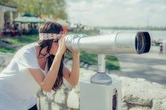 Mujer hermosa que mira sobre ciudad a través del telescopio turístico, belio Fotos de archivo libres de regalías