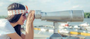 Mujer hermosa que mira sobre ciudad a través del telescopio turístico, belio Imagen de archivo libre de regalías