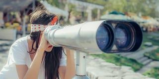 Mujer hermosa que mira sobre ciudad a través del telescopio turístico, belio Fotografía de archivo libre de regalías