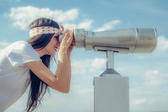 Mujer hermosa que mira sobre ciudad a través del telescopio turístico, belio Fotografía de archivo