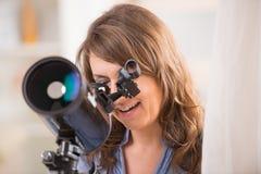 Mujer hermosa que mira a través del telescopio Fotos de archivo libres de regalías