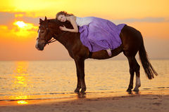 Mujer hermosa que monta un caballo en la puesta del sol en la playa Bea joven Imágenes de archivo libres de regalías