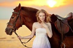 Mujer hermosa que monta un caballo en la puesta del sol en la playa Gir joven imagen de archivo