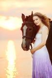 Mujer hermosa que monta un caballo en la puesta del sol en la playa Gir joven Fotos de archivo