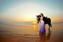 Mujer hermosa que monta un caballo en la puesta del sol en la playa Gir joven Foto de archivo libre de regalías