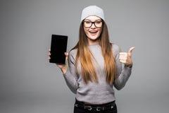 Mujer hermosa que muestra un teléfono elegante con el pulgar para arriba aislado en fondo gris Fotografía de archivo