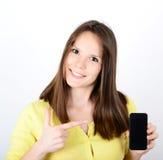 Mujer hermosa que muestra un teléfono elegante con el pulgar para arriba aislado encendido Imagen de archivo