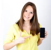 Mujer hermosa que muestra un teléfono elegante con el pulgar para arriba aislado encendido Fotografía de archivo