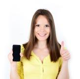 Mujer hermosa que muestra un teléfono elegante con el pulgar para arriba aislado encendido Fotografía de archivo libre de regalías