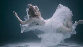 Mujer hermosa que nada bajo el agua en el vestido elegante blanco metrajes