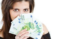 Mujer hermosa que oculta detrás de billetes de banco Imagen de archivo
