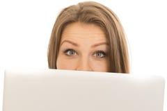 Mujer hermosa que oculta detrás de un ordenador portátil Imagen de archivo libre de regalías
