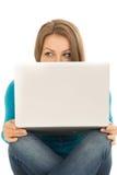 Mujer hermosa que oculta detrás de un ordenador portátil Foto de archivo
