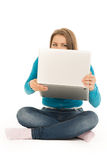 Mujer hermosa que oculta detrás de un ordenador portátil Fotografía de archivo