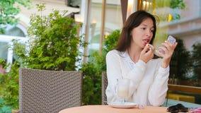 Mujer hermosa que pinta sus labios con el lápiz labial rojo que se sienta en café al aire libre Chica joven con capuchino dulce d metrajes