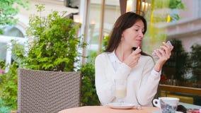 Mujer hermosa que pinta sus labios con el lápiz labial rojo que se sienta en café al aire libre Chica joven con capuchino dulce d almacen de metraje de vídeo