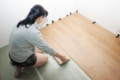 Mujer hermosa que pone el suelo laminado Fotos de archivo