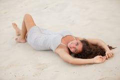 Mujer hermosa que pone en la arena Foto de archivo libre de regalías