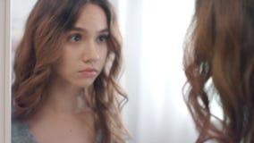 Mujer hermosa que pone en las lentes de contacto en el espejo en el cuarto de baño casero almacen de metraje de vídeo