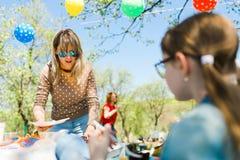 Mujer hermosa que prepara la comida para la fiesta de jardín del verano del cumpleaños imagenes de archivo
